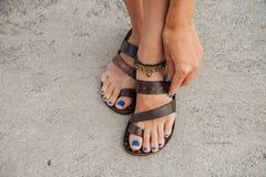 一个女孩的腿有一蓝色修脚的在码头的皮革凉鞋 库存图片