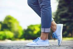 一个女孩的腿牛仔裤和蓝色运动鞋的在边路瓦片,漫步在夏天公园的一个少妇 免版税库存照片