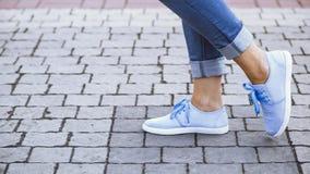 一个女孩的腿牛仔裤和蓝色运动鞋的在边路瓦片,漫步在夏天公园的一个少妇 图库摄影