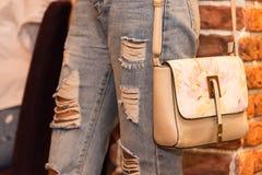一个女孩的腿牛仔裤的和有袋子的 图库摄影