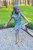 一个女孩的铜雕塑摇摆的在公园 免版税图库摄影