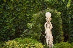 一个女孩的雕塑在一个公园 免版税库存照片