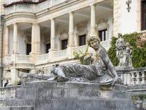 一个女孩的雕象一个垫座的在Peles城堡的庭院里在锡纳亚,在罗马尼亚 库存照片