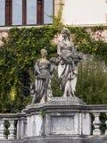 一个女孩的雕象一个垫座的在Peles城堡的庭院里在锡纳亚,在罗马尼亚 库存图片