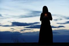 一个女孩的黑剪影一有冠乌鸦的有一个蜡烛的在她的手上 免版税库存照片