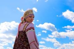 一个女孩的画象俄国民间服装的在天空背景 图库摄影