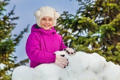 一个女孩的画象在雪墙壁后的在森林里 免版税库存照片