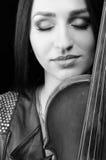 一个女孩的画象有一把小提琴的,有闭合的眼睛的 北京,中国黑白照片 免版税库存照片