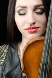 一个女孩的画象有一把小提琴的,有闭合的眼睛的 免版税库存照片