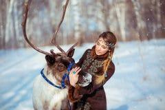 一个女孩的画象有一头驯鹿的在冬天 免版税库存图片
