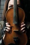 一个女孩的画象有小提琴、仅眼睛和手的能被看见 库存照片