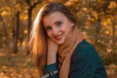 一个女孩的画象有红色唇膏的在您的嘴唇和温暖的围巾在秋天停放特写镜头 库存图片