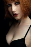 一个女孩的画象有红色头发和雀斑的与红色嘴唇和蓝眼睛与看照相机的黑暗的构成 图库摄影