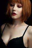 一个女孩的画象有红色头发和雀斑的与红色嘴唇和闭合的眼睛与看照相机的黑暗的构成 免版税库存照片