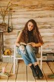 一个女孩的画象有长期的,卷曲,自然头发 女孩读书 库存照片