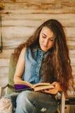 一个女孩的画象有长期的,卷曲,自然头发 女孩读书 免版税图库摄影