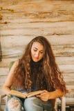 一个女孩的画象有长期的,卷曲,自然头发 女孩读书 免版税库存照片