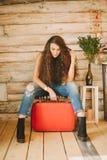 一个女孩的画象有长期的,卷曲,自然头发 红色手提箱 免版税库存照片