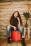 一个女孩的画象有长期的,卷曲,自然头发 红色手提箱 免版税库存图片