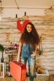 一个女孩的画象有长期的,卷曲,自然头发 红色手提箱 图库摄影