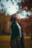 一个女孩的画象有绿色围巾的在背景秋天公园 免版税库存图片