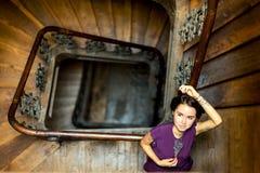 一个女孩的画象栏杆的在黑暗的内部, 免版税库存图片