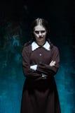 一个女孩的画象校服的当凶手妇女 免版税库存照片