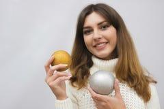 一个女孩的画象毛线衣的有圣诞节球的 免版税库存照片