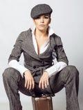 一个女孩的画象灰色衣服的坐葡萄酒手提箱 免版税库存图片
