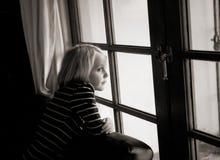 一个女孩看窗口。她看一看严肃的他 库存图片