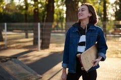 一个女孩站立与在牛仔布夹克的一个滑板 库存图片