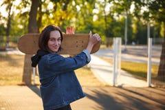 一个女孩站立与在牛仔布夹克的一个滑板 免版税库存图片
