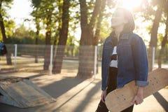 一个女孩站立与在牛仔布夹克的一个滑板 库存照片