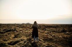 一个女孩站立与她并且为风景照相 免版税图库摄影