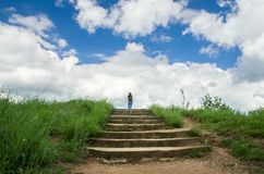 一个女孩站立在一个石楼梯顶部并且看天空 免版税库存图片