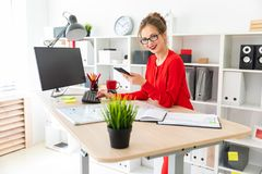 一个女孩站立在一张桌上在办公室,拿着一个黑标志和一个电话在她的手上 女孩与a一起使用 免版税库存图片