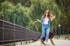 一个女孩走与一条狗在公园 免版税库存照片