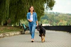 一个女孩走与一条狗在公园 免版税库存图片