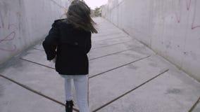 一个女孩通过一个黑暗的具体隧道跑到发光的末端 股票录像