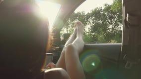 一个女孩通过伸出她的在一辆开窗口汽车的腿 年轻女人喜欢乘汽车,旅行概念,生活方式旅行 股票视频