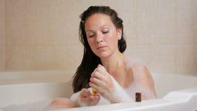 一个女孩采取与泡沫的浴和有香波的洗涤的头发 大白色浴和一个小瓶香波在 影视素材