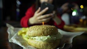 一个女孩采取在您的智能手机的图片您的汉堡的在一个人陪同下在酒吧 影视素材