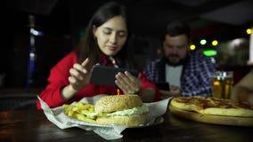 一个女孩采取在您的智能手机的图片您的汉堡的在一个人陪同下在酒吧 股票录像