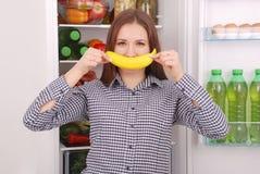 一个女孩阻止香蕉对她的嘴,仿效微笑 免版税库存照片