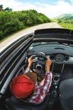 一个女孩驾驶沿在树中绿色丛林的一条柏油路乘坐的一辆美丽的汽车 库存图片