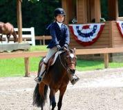 一个女孩骑在Germantown慈善马展示的一匹马 免版税图库摄影