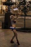 一个女孩骗子在城市的中心安排一个火热的展示 免版税库存照片