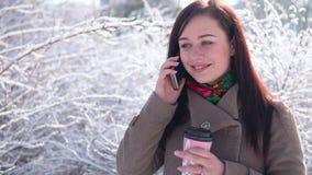 一个女孩,外套的,通过冬天公园漫步,写消息并且喝咖啡 影视素材