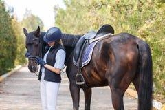 一个女孩,有一匹马的在公园,拥抱她的面孔 免版税库存照片
