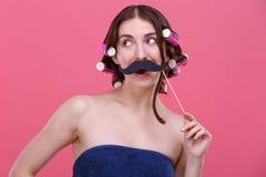 一个女孩,有在头发的卷发的人的,握在面孔的纸髭,微笑着并且看  图库摄影
